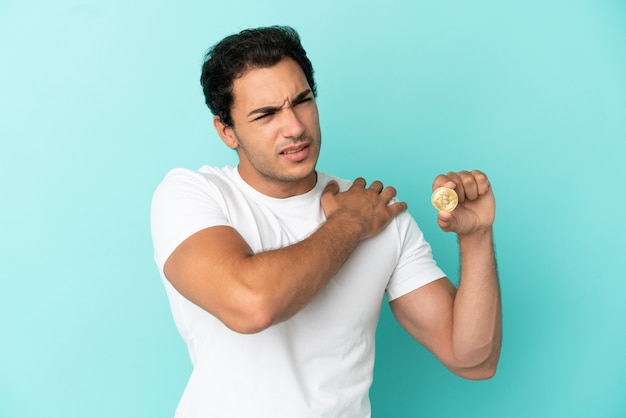 Young man holding a bitcoin over isolated blue background suffering from pain in shoulder for having made an effort