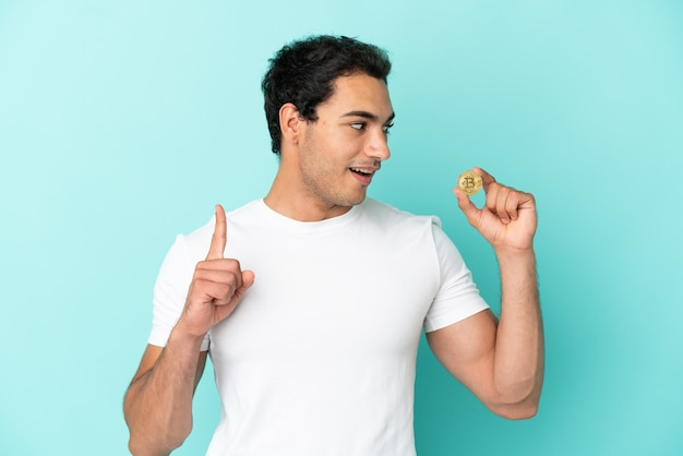 Young man holding a bitcoin over isolated blue background thinking an idea pointing the finger up