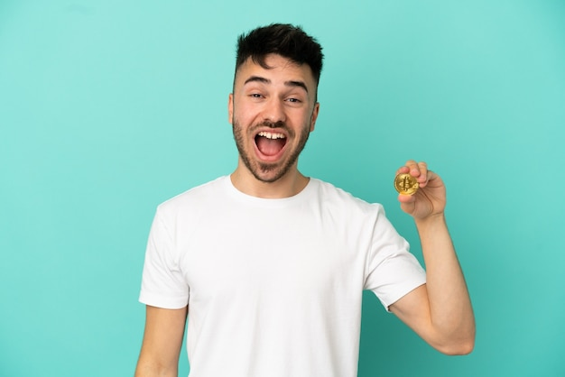Young man holding a bitcoin isolated on blue background with surprise facial expression