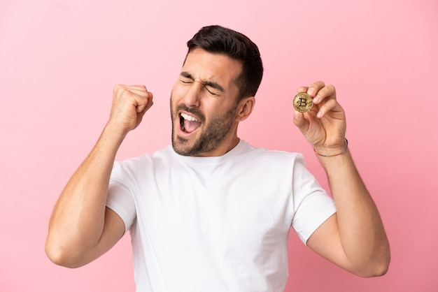 Young man holding a bitcoin isolated on pink background celebrating a victory