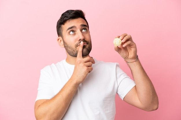 Young man holding a bitcoin isolated on pink background having doubts while looking up