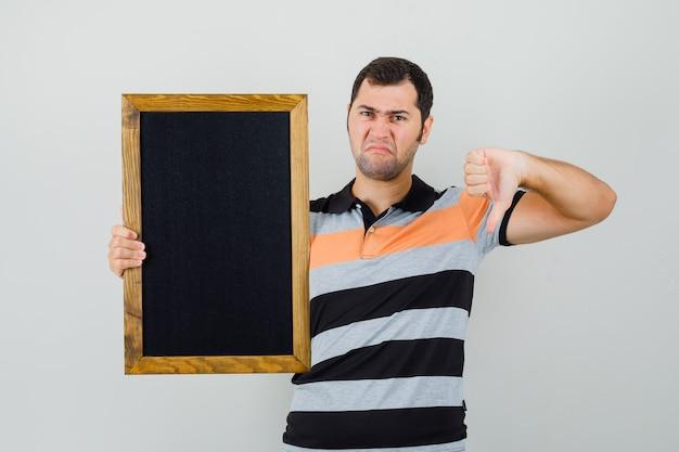 Tシャツで親指を下に見せながら黒いフレームを保持し、不機嫌そうに見える若い男。