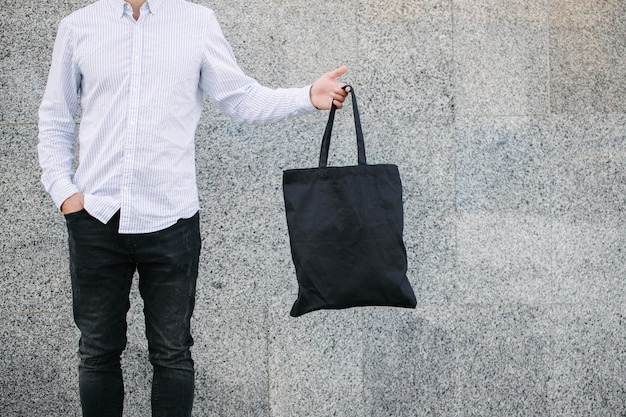 Young man holding black textile eco bag against urban city background. . ecology or environment protection concept. black eco bag for your design or logo mock up