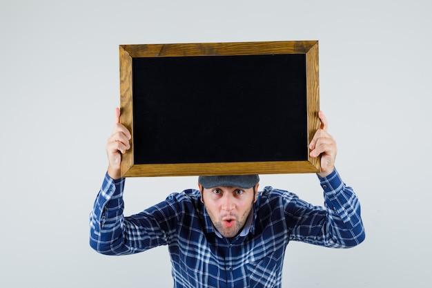 シャツ、キャップで頭の上に黒板を持って、驚いて、正面図を見て若い男。