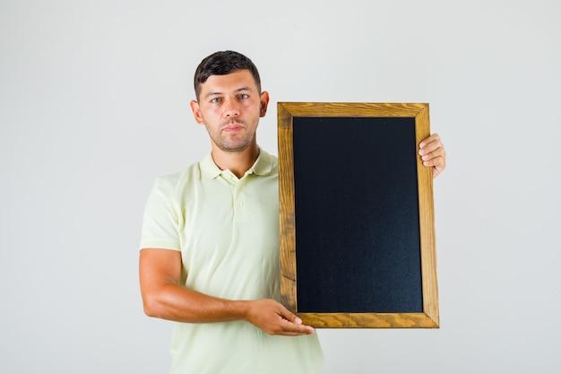 若い男が黒板を押しながらtシャツでカメラ目線
