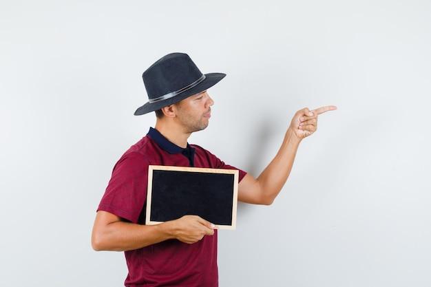 칠판을 들고 티셔츠, 모자 전면 보기에서 측면을 가리키는 젊은 남자.