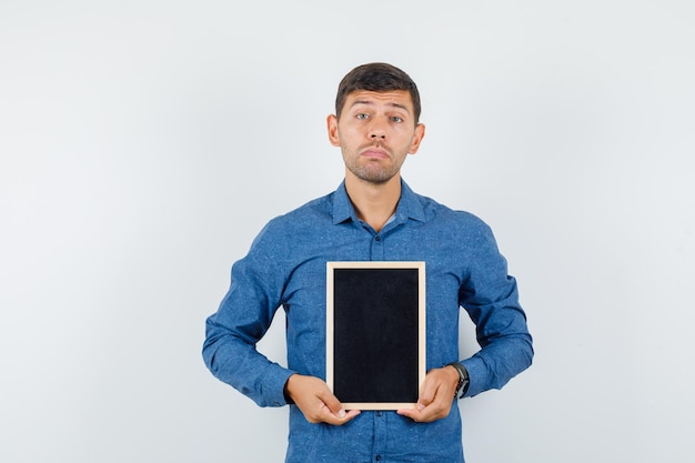 Young man holding blackboard in blue shirt and looking helpless. front view.