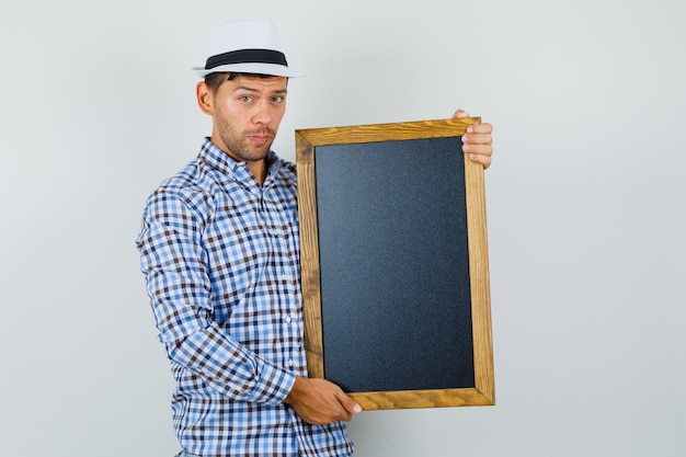 Young man holding blackboard in checked shirt