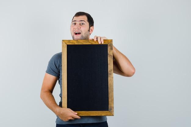 회색 티셔츠에 칠판을 들고 유쾌한 찾고 젊은 남자