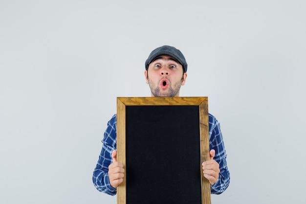 シャツ、キャップで黒板を保持し、驚いたように見える若い男、正面図。