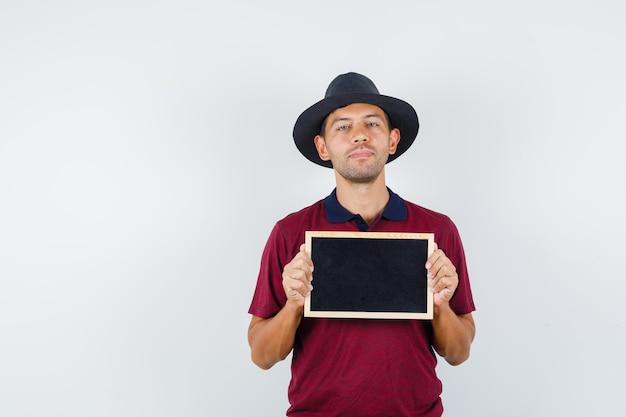 티셔츠, 모자, 자신감 찾고 칠판을 들고 젊은 남자. 전면보기.