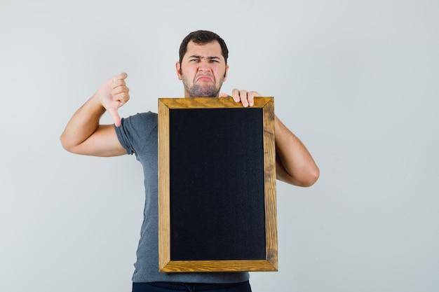 회색 티셔츠에 아래로 엄지 손가락을 보여주는 칠판을 들고 불만을 찾는 젊은 남자