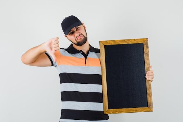 Giovane uomo con lavagna, mostrando il pollice verso il basso in t-shirt, berretto e guardando insoddisfatto, vista frontale.