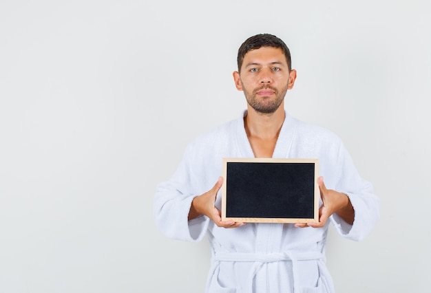 Young man holding blackboard in white bathrobe and looking serious. front view.