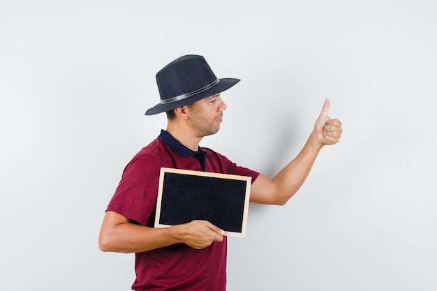 티셔츠, 모자, 전면 보기에 엄지손가락으로 칠판을 들고 있는 젊은 남자.
