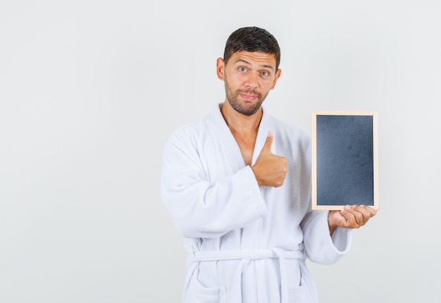 흰 가운 전면보기에서 엄지 손가락으로 칠판을 들고 젊은 남자.