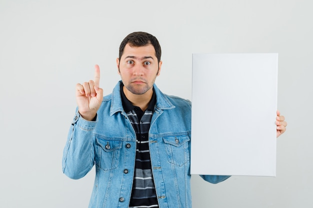 Young man holding blank canvas, pointing up in t-shirt, jacket and looking curious