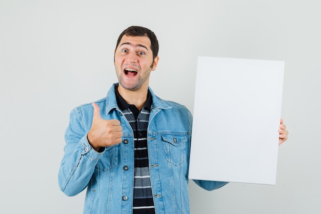 Young man holding blank canvas, showing thumb up in t-shirt, jacket and looking cheerful