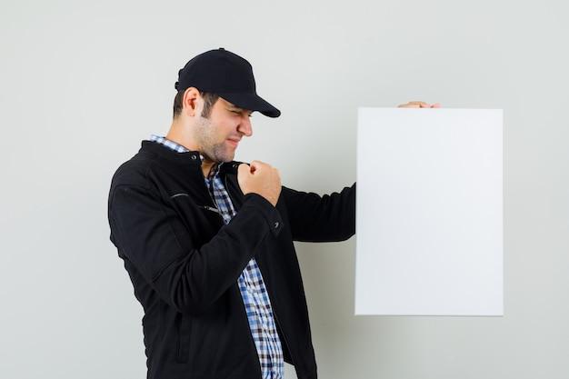 Giovane che tiene tela bianca, mostrando il gesto del vincitore in camicia, giacca, berretto e sembra fortunato.