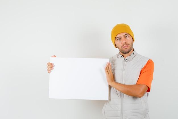 Giovane che tiene tela bianca in t-shirt, giacca, cappello e che sembra calmo, vista frontale.