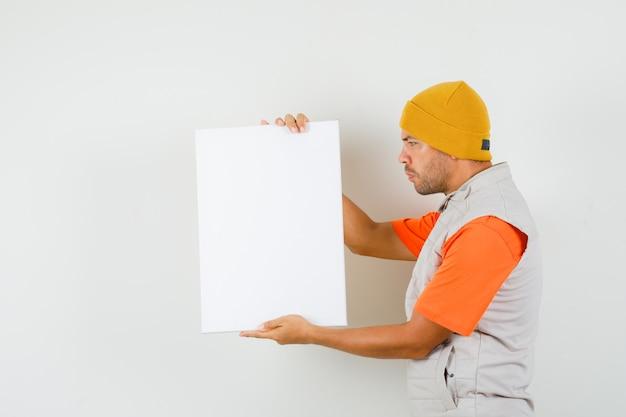 Giovane che tiene tela bianca in t-shirt, giacca, cappello e guardando concentrato.