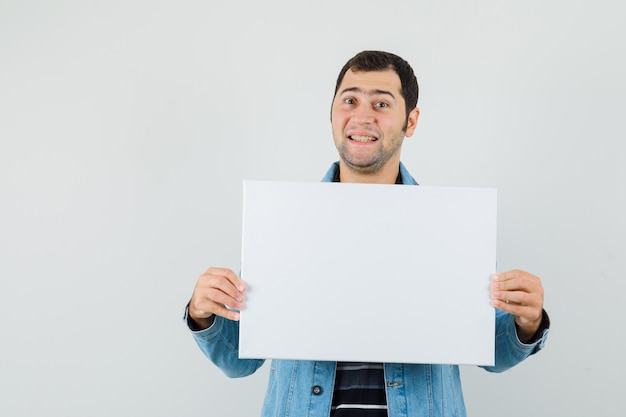 Young man holding blank canvas in t-shirt, jacket and looking merry