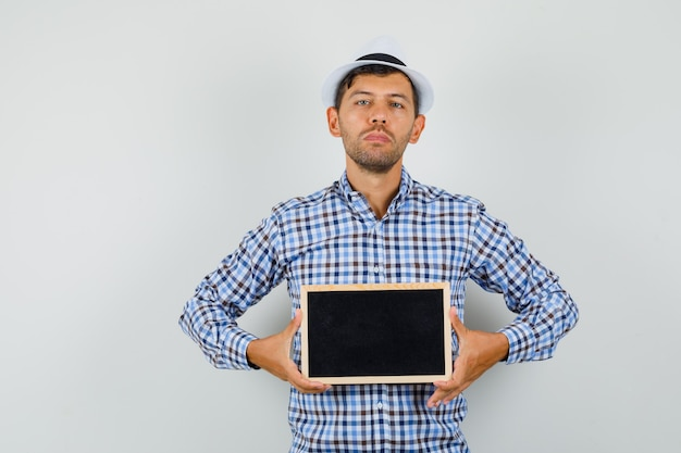 Young man holding blank frame in checked shirt