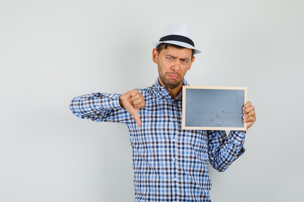 Young man holding blank frame, showing thumb down in checked shirt