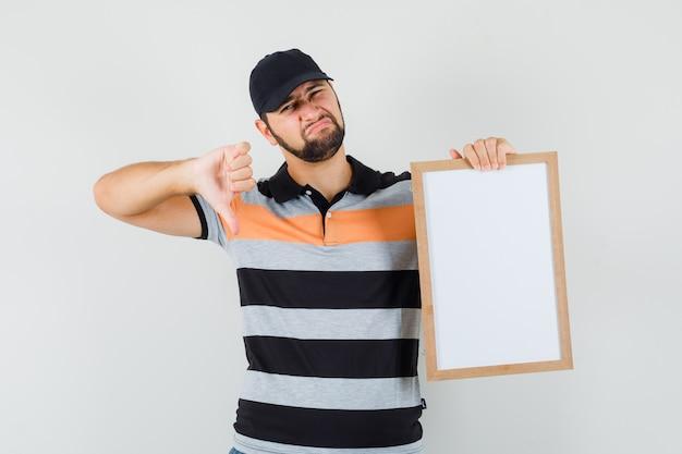 Giovane che tiene la cornice vuota, mostrando il pollice verso il basso in maglietta, berretto e guardando scontento. vista frontale.