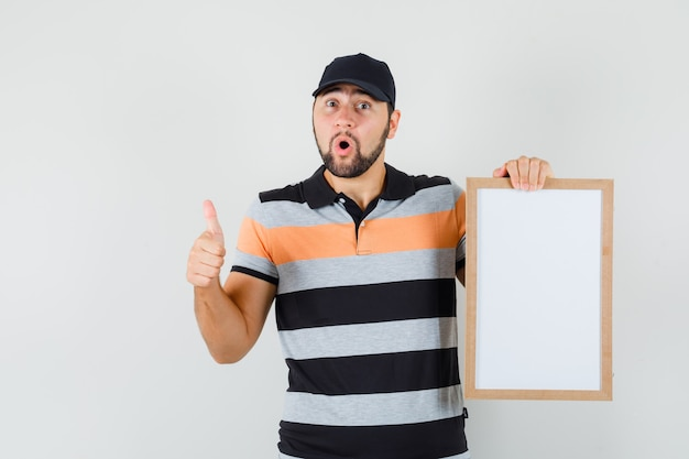 Young man holding blank frame, showing thumb up in t-shirt, cap and looking amazed , front view.