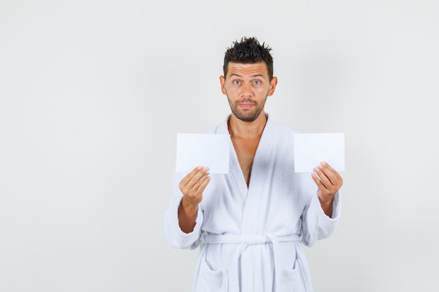 Young man holding blank paper sheets in white bathrobe front view.