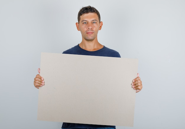 Young man holding blank poster in dark blue t-shirt and looking hopeful. front view.