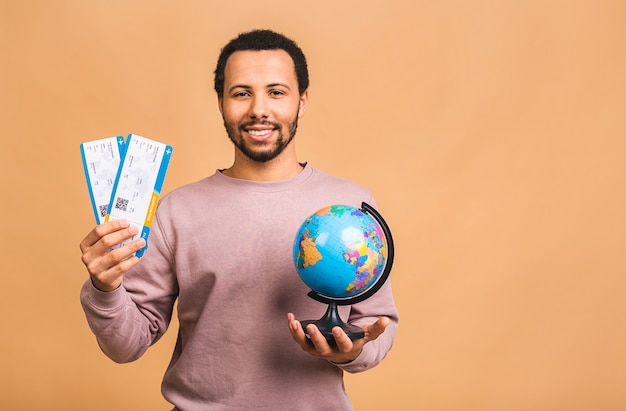 Young man holding boarding pass tickets and globe isolated over beige