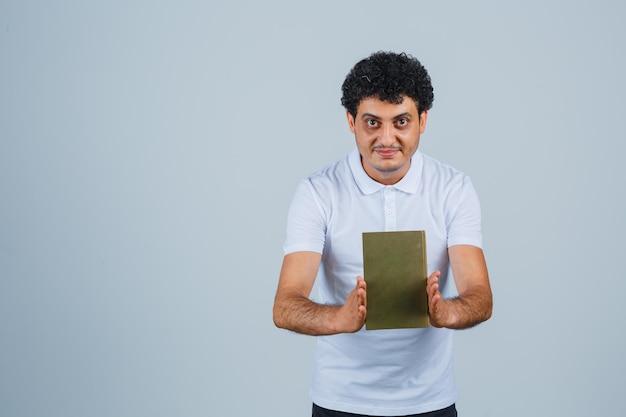 흰색 티셔츠에 책을 들고 쾌활한 젊은 남자. 전면보기.