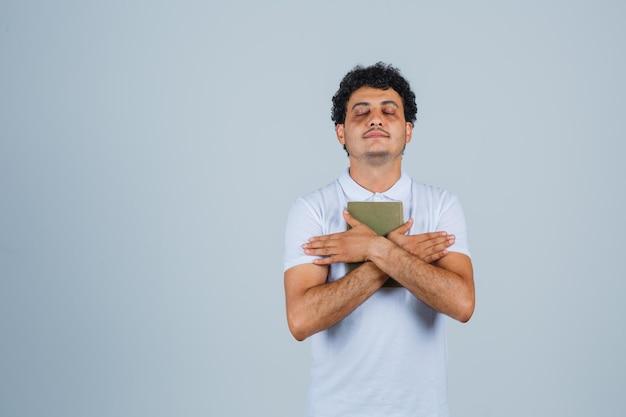 흰색 티셔츠에 책을 들고 평화롭게 보이는 젊은 남자. 전면보기.