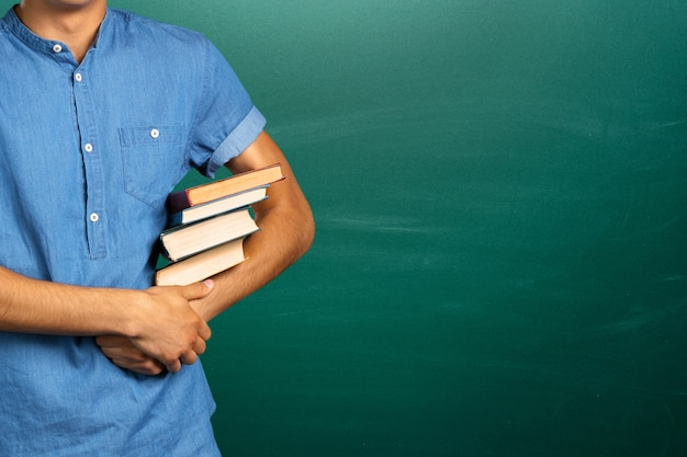 Young man holding books and background with copyspace