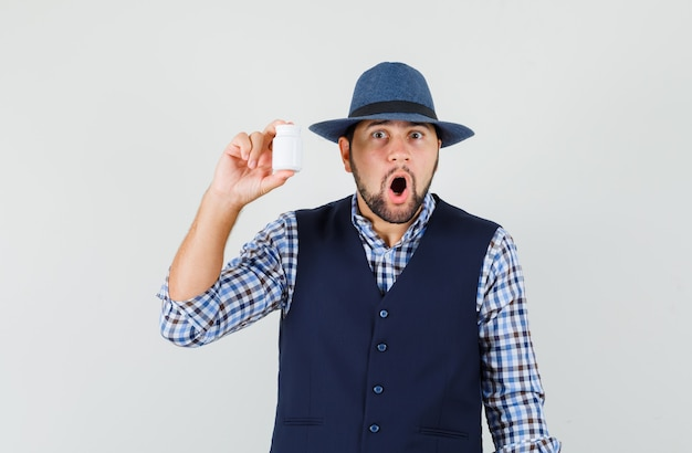 Молодой человек держит бутылку таблеток в рубашке, жилете, шляпе и выглядит шокированным. передний план.