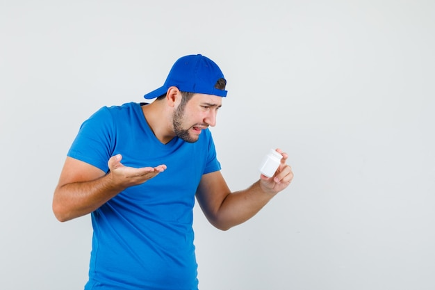 Young man holding bottle of pills in blue t-shirt and cap and looking depressed