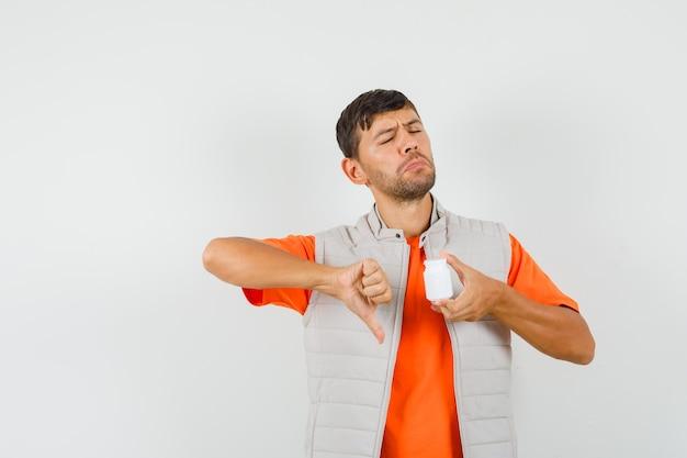Giovane che tiene una bottiglia di pillole, mostrando il pollice verso il basso in maglietta, giacca e guardando malcontento. vista frontale.
