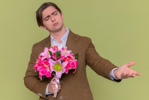 Giovane che tiene il mazzo di fiori che osserva da parte confuso con il braccio alzato andando a congratularsi con la giornata internazionale della donna in piedi sopra la parete verde