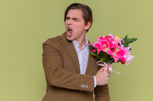 Young man holding bouquet of flowers looking aside shouting with aggressive expression
