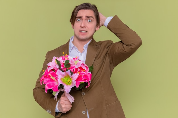 Young man holding bouquet of flowers looking at camera surprised