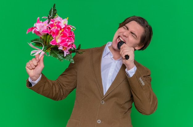 Молодой человек, держащий букет цветов и микрофон, счастлив и взволнован, собираясь поздравить с международным женским днем, стоя над зеленой стеной