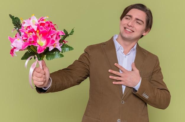젊은 남자가 꽃의 꽃다발을 들고 옆으로 웃고 감사하는 느낌을 웃고