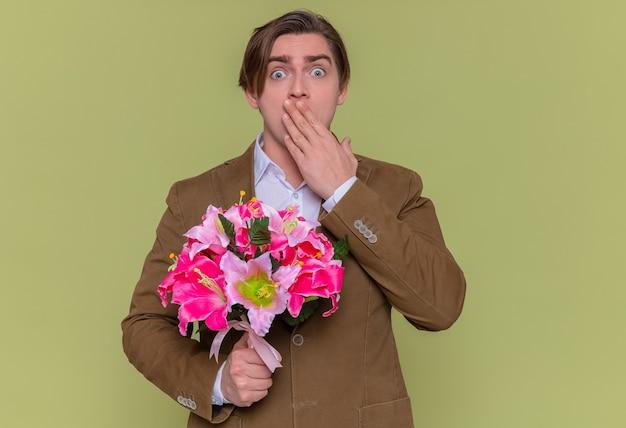 카메라를보고 꽃의 꽃다발을 들고 젊은 남자가 입을 덮고 충격을 받고
