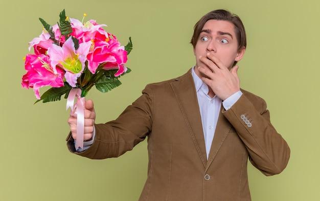 Молодой человек держит букет цветов, глядя на него с удивлением, прикрывая рот рукой
