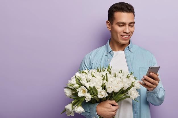 Молодой человек держит букет белых цветов
