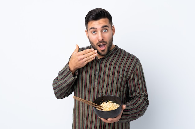 Young man holding a bowl of noodles over isolated wall