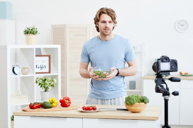 Молодой человек держит миску с салатом и рассказывает, как приготовить овощной салат онлайн на камеру на кухне