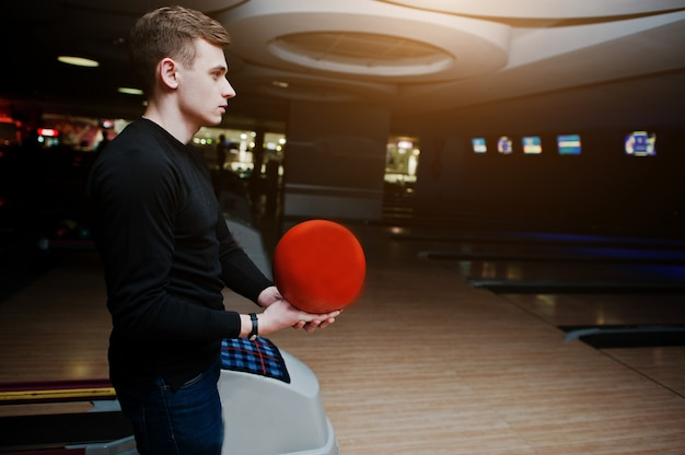 Young man holding a bowling ball standing against bowling alleys with ultraviolet light.